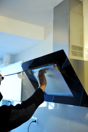 fume: Specialist worker by installing a modern fume extractor hood in the kitchen