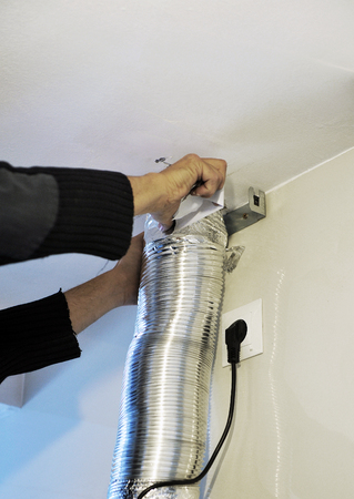 extractor: Worker installing the aluminum tube for extractor hood in the kitchen