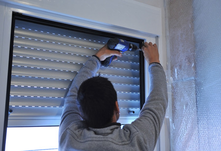 Travailleur de la construction à l'aide de tournevis électrique pour installer une fenêtre d'aluminium Banque d'images - 53374445