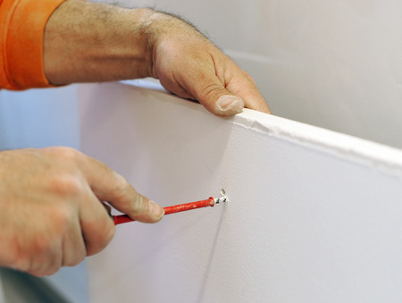 making hole: Plasterer making a hole in a plasterboard