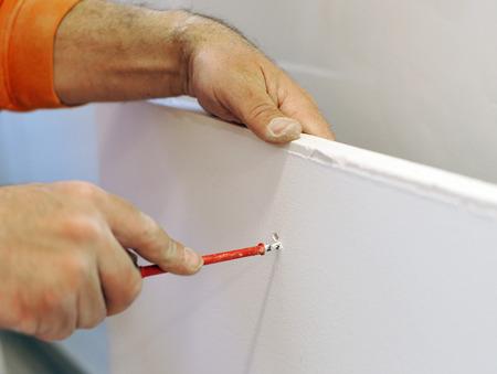 plasterer: Plasterer making a hole in a plasterboard