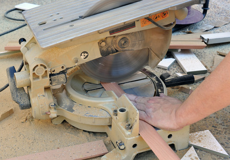 miter: Carpenter cutting profiles with miter saw Stock Photo