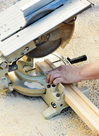 miter: Carpenter cutting wooden profiles with miter saw
