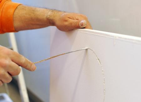 plasterer: Plasterer cutting a plasterboard Stock Photo