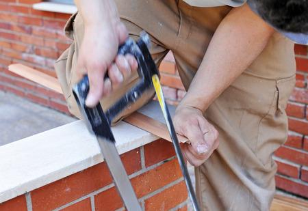 serrucho: Carpintero cortar un perfil de aluminio con sierra de mano Foto de archivo