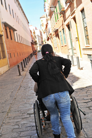 debility: Elderly woman in wheelchair and his assistant in a street of rough pavement