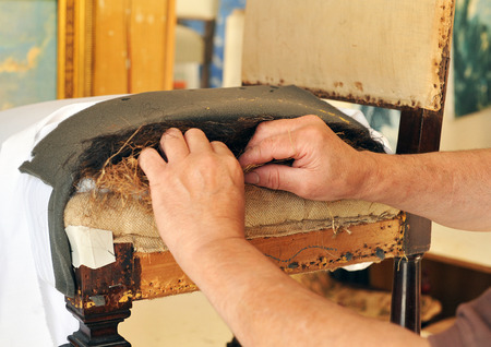 Upholsterer repairing an old chair seat Standard-Bild