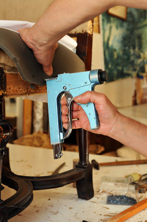 Upholsterer using a manual stapler to repair a chair in his workshop Stock Photo