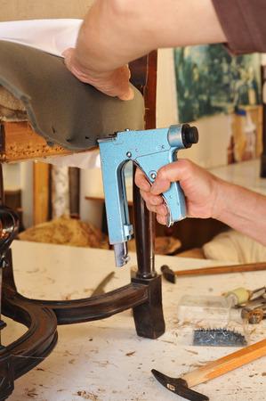 An upholsterer repairing an armchair with stapler