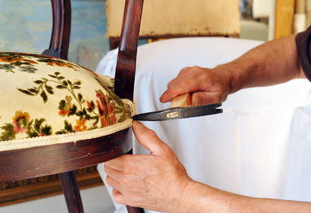 Traditional upholsterer changing the seat upholstery of a chair Stock Photo