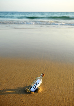 approbate: Bottle on the beach with an affirmative answer inside, okey Stock Photo