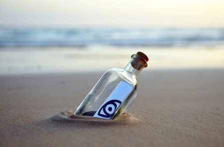 all seeing eye: Bottle with message on the beach, all seeing eye