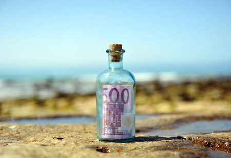 Old glass bottle with 500 euro banknote inside on the rocks of the beach