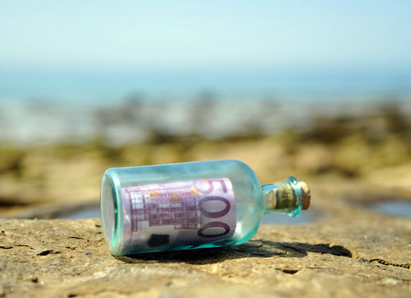 Old glass bottle with 500 euro banknote inside