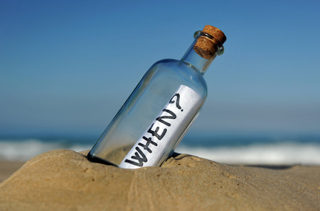 when: Bottle with question on the sand, when