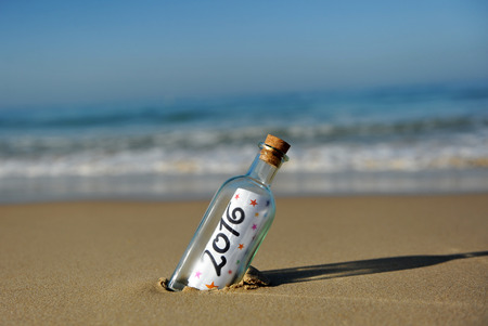 New year party, bottle with message on the beach, 2016 免版税图像