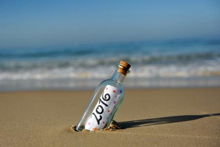 Party des neuen Jahres, Flasche mit Meldung auf dem Strand, 2016 Standard-Bild - 43691418
