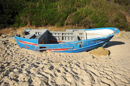 southern europe: Coasts of southern Europe, boat wrecked on the sea shore, immigration, hopeless Stock Photo