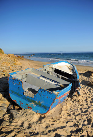 southern europe: Illegal immigration, boat wrecked on the sea shore, Strait of Gibraltar, southern Europe Stock Photo