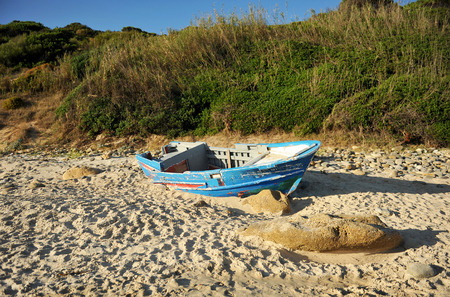 wrecked: Illegal immigration, boat wrecked on the sea shore, Strait of Gibraltar, southern Europe Stock Photo