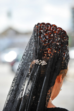 holy week in seville: Woman with veil and ornamental comb for Good Friday, Holy Week, Seville, Spain