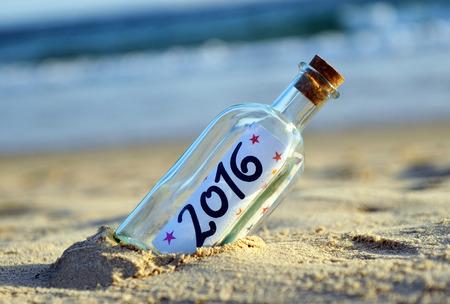 2016 Happy new year, bottle on beach Фото со стока