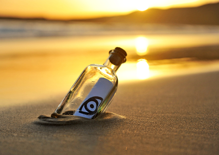 casualness: Bottle with eye icon at the beach, sunset Stock Photo