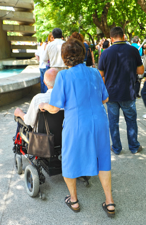 accompanied: Disabled man in a wheelchair accompanied by his wife Stock Photo