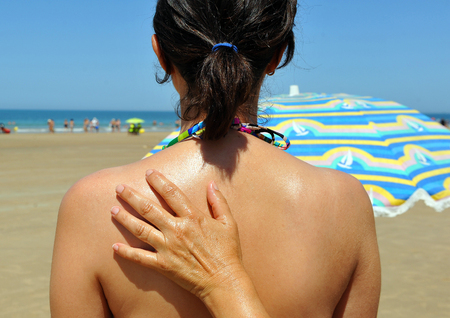 uva: Application of sunscream on the skin of a young woman, beware the sun Stock Photo