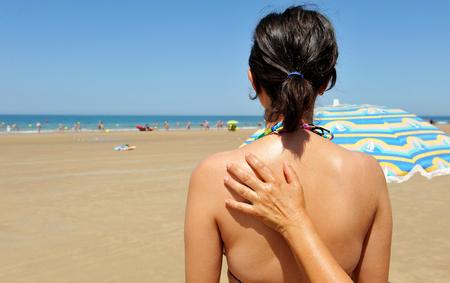 radiacion solar: Cuidado con el sol, la aplicación de protector solar en la piel de una mujer joven en la playa