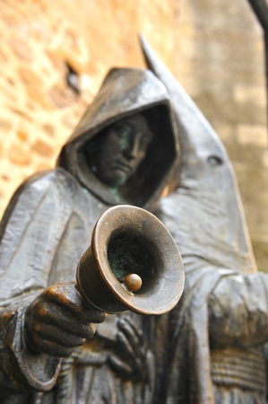 bell bronze bell: Bronze sculpture of Nazarene with a bell, Easter Week in Caceres, Spain