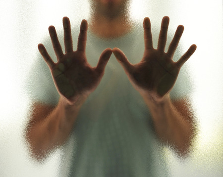 life threatening: The man behind the glass with both hands outstretched
