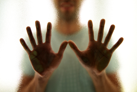 The man behind the glass with both hands outstretched