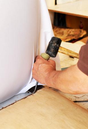 upholsterer: Upholsterer eliminating the old staples of the chair Stock Photo