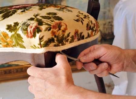 Traditional upholsterer finishing work, changing the upholstery of an antique chair seat