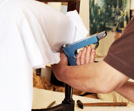 upholsterer: An upholsterer repairing an old armchair with stapler