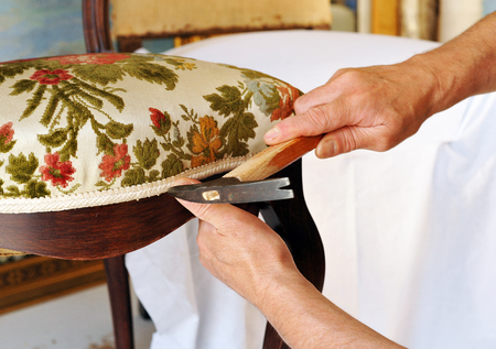 Traditional upholsterer changing the seat upholstery of a chair Standard-Bild