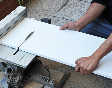 cable cutter: Carpenter cutting a white board with electric saw disk
