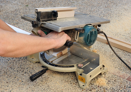 miter: Carpenter cutting a white wooden profile with the miter saw for the renovation of the house