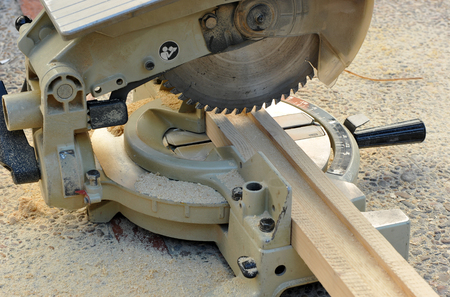 miter: Closeup of a electric miter saw prepared to cut a profile of wood Stock Photo