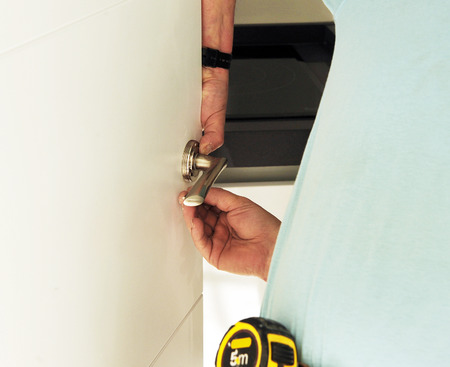 cabinet maker: Carpenter placing a new door handle