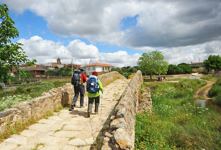 Pilgrims couple crossing the stone bridge in Aldea del Cano, Via de la Plata, Camino de Santiago in the province of Caceres, Spain