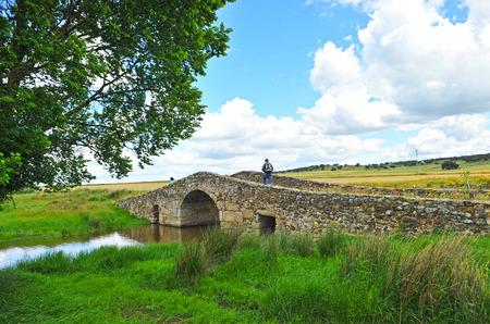 cano: Camino de Santiago, Pilgrims crossing a Roman bridge, Aldea del Cano, province of Caceres, Spain Stock Photo