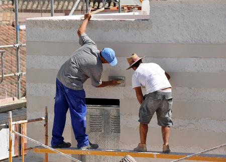 Deux maçons travaillant sur la construction d'une maison, façade de ciment blanc Banque d'images - 53338857