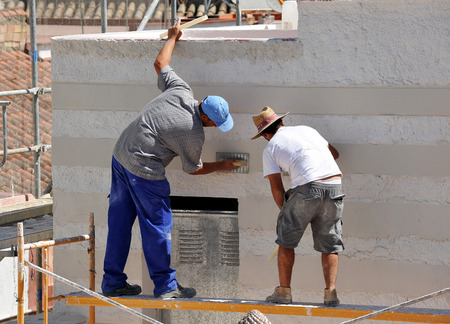 Two bricklayers working on building a house, facade of white cement
