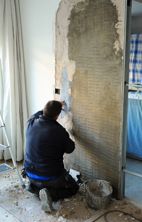 sliding door: Bricklayer placing a cassette compartment for new sliding door Stock Photo