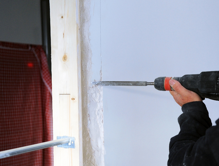 undercut: Bricklayer making an undercut for electrical conduits in the wall with an electric hammer