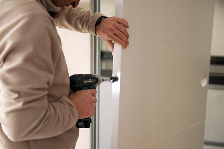 sliding door: Carpenter placing a rubber bumper on the new sliding door