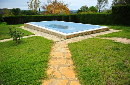 Pool im Garten eines Landhauses mit einer Plane zum Schutz im Winter