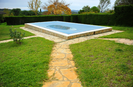 Pool in the garden of a country house with a tarp for protection in winter